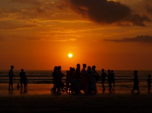 hare krishnas passing by at a sunset in Legian beach